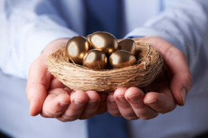 Businessman Holding Nest Full Of Golden Eggs
